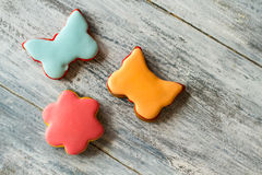 Little cookies with colorful glaze. Biscuits shaped as butterflies. Dessert for children. Sweets on gray table Stock Image