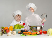 Little cooks by the kitchen table in steam Stock Image