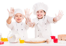 Little cooks in uniform making dough with hands up Stock Photos