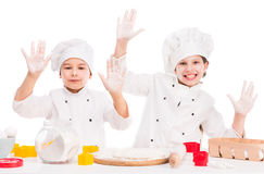 Little cooks in uniform making dough with hands up Royalty Free Stock Photo