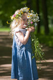 Little coquette. Small smiling girl in a wreath is hidden a bunch of flowers stock photos