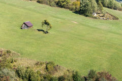 Little cottage on green pasture Royalty Free Stock Image