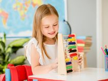 Little counting on the colourful abacus in the school classroom royalty free stock photo