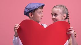 Little couple hiding behind big red heart and kissing, tender love at young age. Stock footage stock video footage