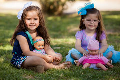 Little cousins playing with dolls Royalty Free Stock Photography