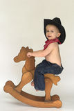 Little Cowboy. Image of cute toddler wearing a black cowboy hat, red bandanna and jeans, riding a wooden rocking horse Royalty Free Stock Images