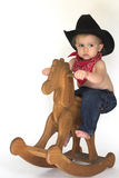 Little Cowboy. Image of cute toddler wearing a black cowboy hat, red bandanna and jeans, riding a wooden rocking horse Royalty Free Stock Photo