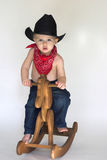 Little Cowboy. Image of cute toddler wearing a black cowboy hat, red bandanna and jeans, riding a wooden rocking horse Royalty Free Stock Image