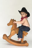 Little Cowboy. Image of cute toddler wearing a black cowboy hat, red bandanna and jeans, riding a wooden rocking horse Stock Images