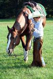 Little Cowboy. A little cowboy with his brown horse in green grass stock images