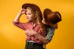 Little cowboy embracing stylish cowgirl,. Isolated on yellow stock image