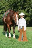 Little Cowboy with Horse. A little boy dressed up like a cowboy posing with his brown horse in a pasture stock photography