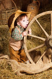 Little Cowboy licks wheel Royalty Free Stock Photo