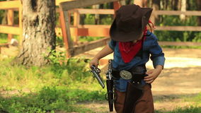 Little Cowboy puts the gun in his holster stock footage