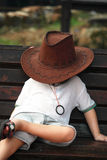 Little Cowboy Sleeping Portrait. Asian little young boy sleeping on bench with cowboy hat Stock Photos