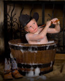 Little cowboy taking bubble bath. Little boy scrubbing in barrel Stock Photography
