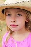 Little Cowgirl. A closeup of a little 6 year old somber cowgirl with blond hair wearing a large cowboy hat in pink. Shallow depth of field Royalty Free Stock Photo