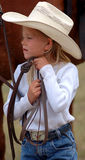 Little Cowgirl Adjusting Her Hat. Young cowgirl adjusting her hat while holding the reins of horse behind her stock photography