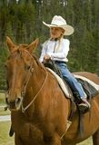 Little Cowgirl on Her Horse. Little cowgirl out for a ride on her bay horse - focus on the girl stock photo