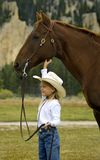 Little Cowgirl and Her Horse. Little cowgirl holding her horse and scratching it under the jaw royalty free stock photo