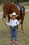 Little Cowgirl Holding Chestnut/Sorrel Horse. Young cowgirl holding the reins of a chestnut/sorrel horse standing behind her stock image