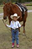 Little Cowgirl Holding Chestnut/Sorrel Horse stock image