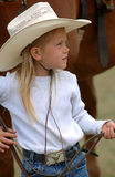 Little Cowgirl Holding Reins. Young cowgirl holding the reins of horse behind her stock photos