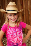 Little cowgirl in a straw hat. A young cute little blond farm girl in pink shirt, and a straw cowboy hat. Shallow depth of field Royalty Free Stock Image