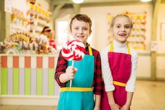 Little craftmen are having fun in candy store. Happy children with handmade lollipop. Fresh cooked sugar caramel Stock Photos