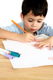 Little Creativity. A young boy engross in his drawing on paper against white background Stock Image