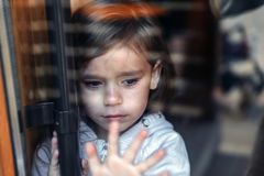Little crying girl standing behind the glass door and looking for parents. Sad child royalty free stock photo