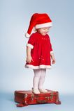 Little crying girl standing on suitcase with gifts Royalty Free Stock Photography