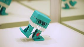 Little cubic funny turquoise robot walking and dancing. Plastic robot. With drawn glasses and tools stock video