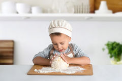 The little culinary specialist with the dough. The little culinary specialist kneads the dough with both hands Royalty Free Stock Photography