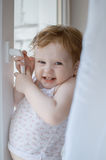 The little cunning girl tries to open a window Stock Images