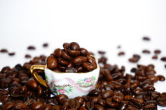 Little cup with coffee beans on grunge background Stock Images