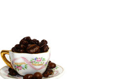 Little cup with coffee beans on grunge on white background Royalty Free Stock Photos