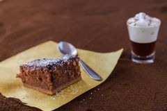 Little cup of piccolo latte macchiato on a table covered with ground coffee as a background and chocolate brownie with stock photography