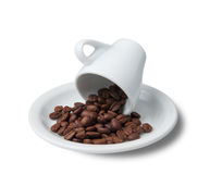 Little cup with scattered coffee beans lying on saucer Royalty Free Stock Image