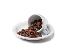 Little cup with scattered coffee beans lying on saucer Stock Images