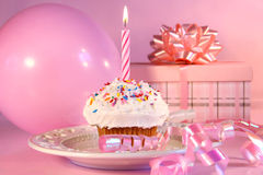 Little cupcake with sprinkles. Little cupcake with candle, balloon and gift on pink background royalty free stock photo