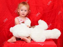 Little curious blond girl and a stuffed teddy bear Royalty Free Stock Photography