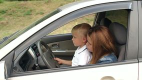 A little curious boy sits with his mother at the wheel of the car. Slow motion. A little curious boy sits with his mother at the wheel of a car and turns on the stock video