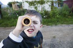 Little curious explorer, boy looking at skies through the cardboard spyglass Royalty Free Stock Photos