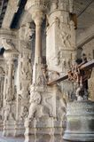 A little curious monkey Peeps out from behind the columns of an ancient Indian temple royalty free stock photo