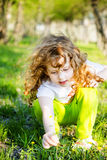 Little curly baby pluck yellow flowers. Stock Photo