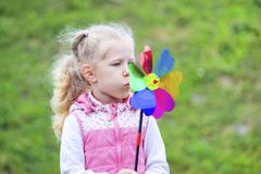 Little blonde girl holding multicolored pinwheel in her ha. Little curly blonde girl holding multicolored pinwheel in her hands Stock Image