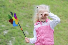 Little girl holding multicolored pinwheel in her hands. royalty free stock image