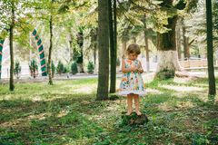 Little curly blonde girl playing outdoors. Royalty Free Stock Photos