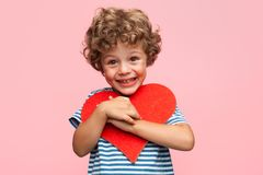 Charming boy posing with heart. Little curly boy holding heart application and laughing at camera on pink background Stock Photography